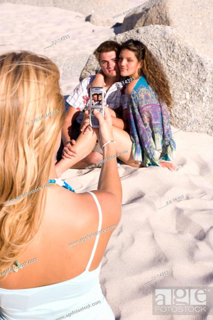 Stock Photo: Young woman taking photograph with mobile phone of friends embracing on beach.