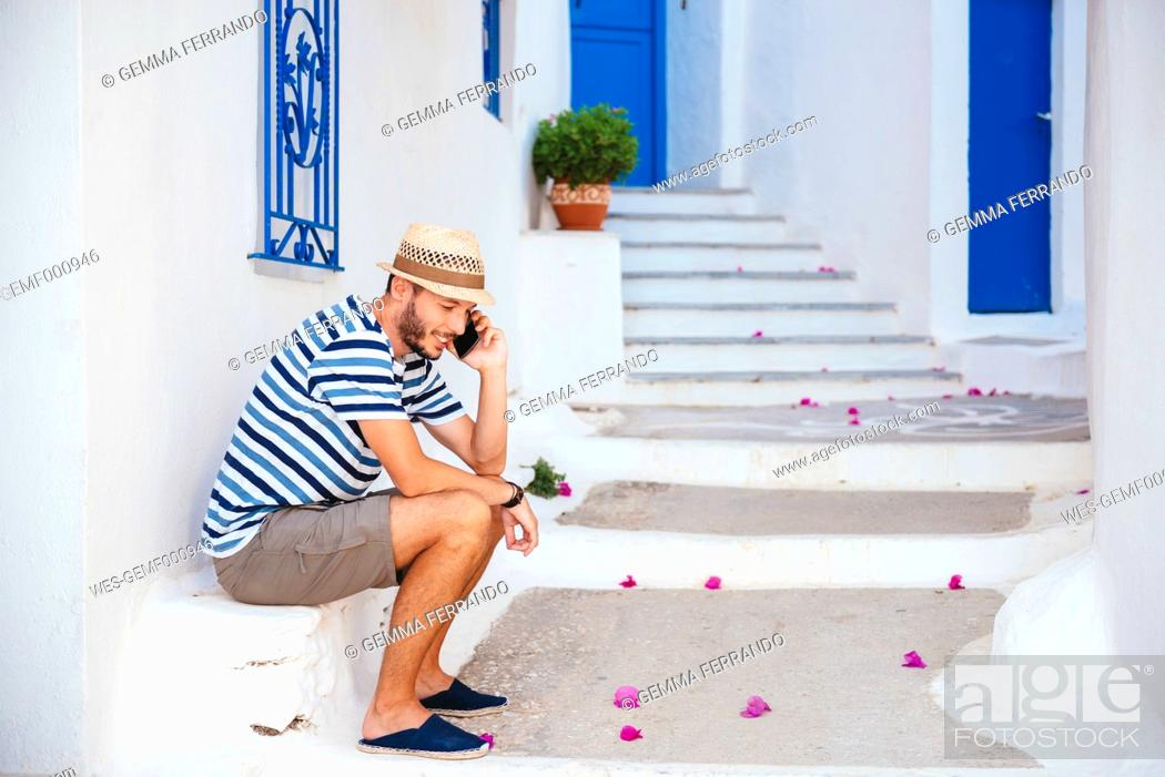 Stock Photo: Greece, Amorgos island, young man talking on cell phone.