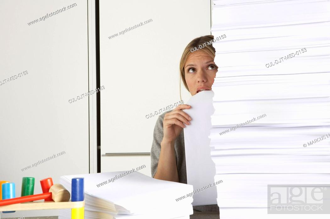 Stock Photo: Young woman working from home with huge pile of paper.