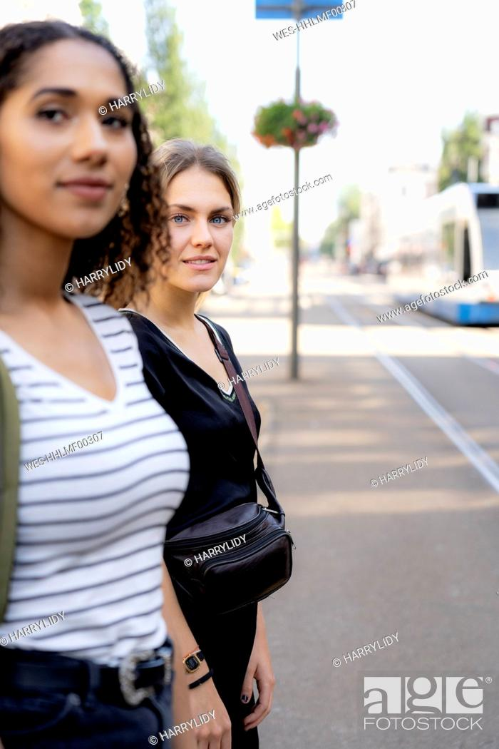 Photo de stock: Two young women crossing street in the city.
