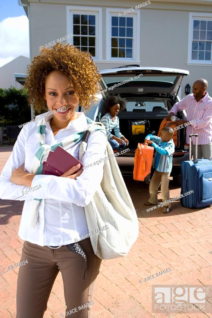 Stock Photo: Woman in driveway with passports, family loading luggage into car in background, smiling, portrait.
