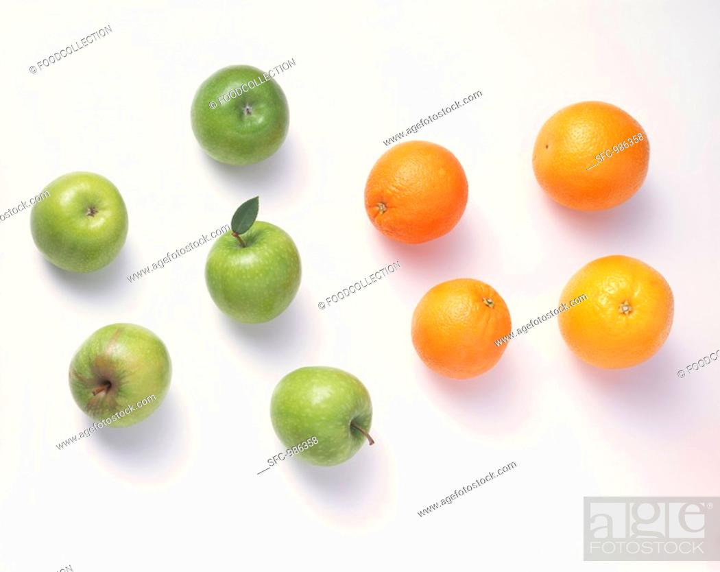 Imagen: Five green apples & four oranges against a white background.