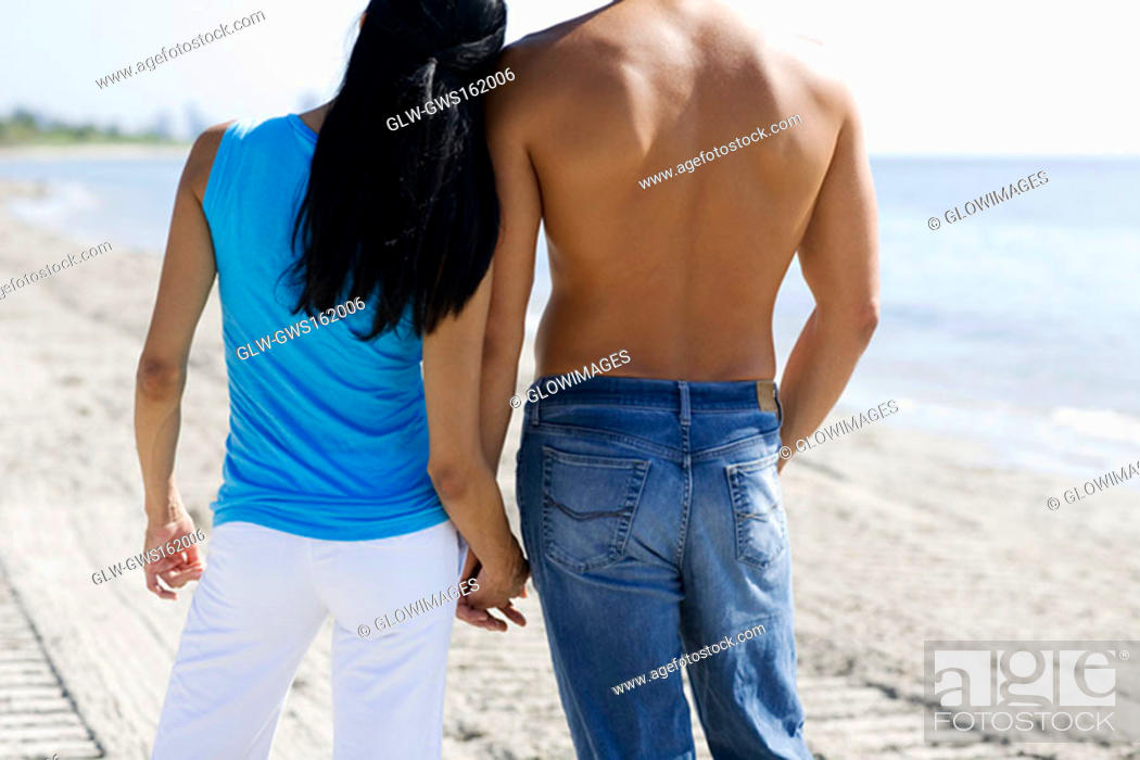 Stock Photo: Rear view of a man and a woman holding hands on the beach.