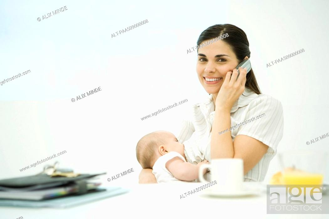 Stock Photo: Woman sitting at breakfast table, breast feeding baby, using cell phone, smiling at camera.