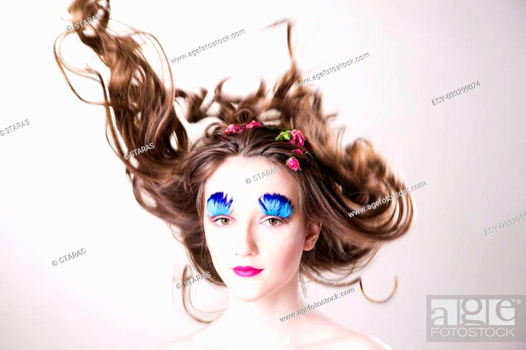 Stock Photo: Portrait of a beautiful young woman on a gray background. Girl with creative make-up and hairstyle with flowers.