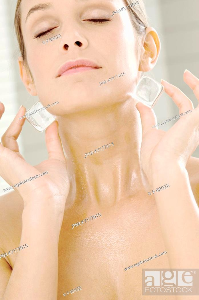 Stock Photo: Close-up of a young woman rubbing ice cubes on her neck.