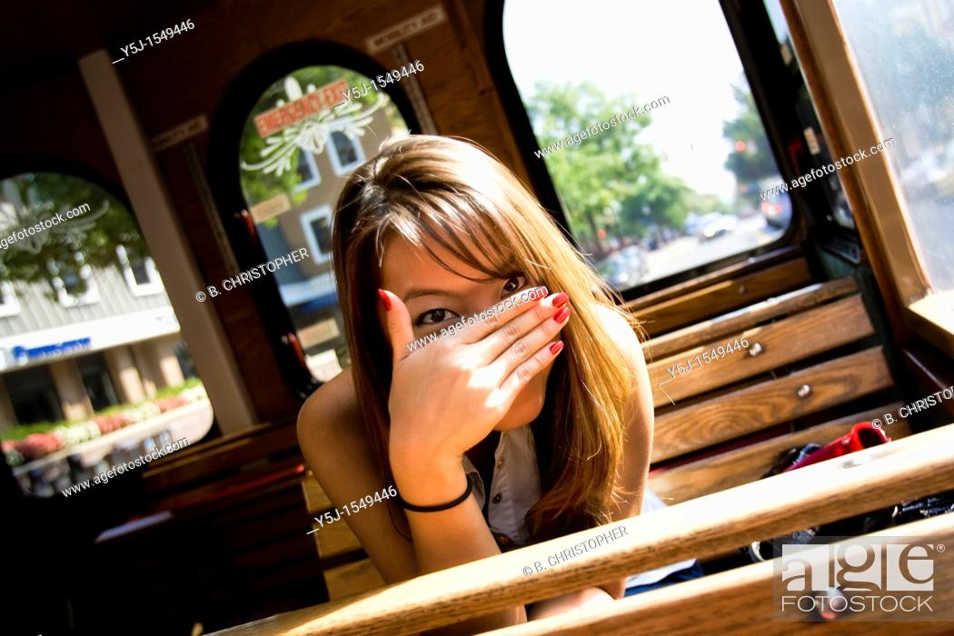 Stock Photo: Young Asian female sitting inside a trolley, hiding her face behind hand.