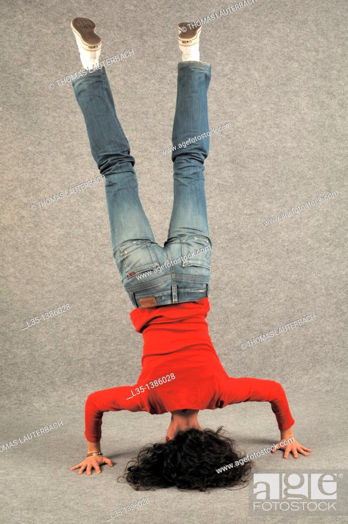 Stock Photo: Young woman doing a headstand.