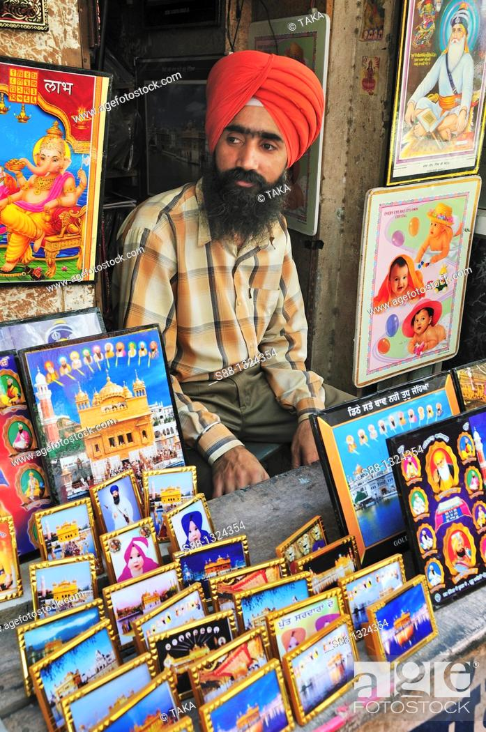 Stock Photo: Sikh man sell holly pictures from Amritsar.