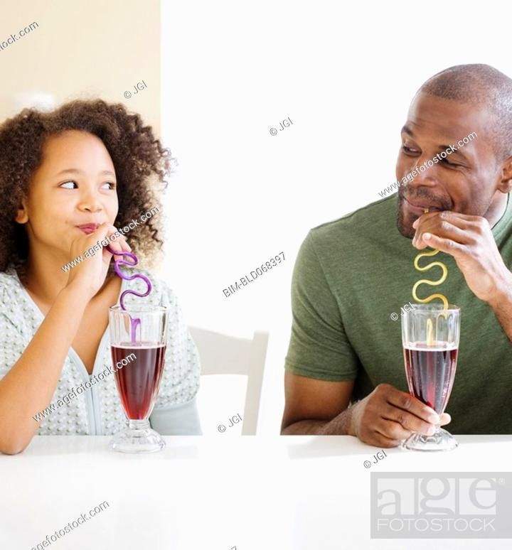 Stock Photo: African father and daughter drinking with straws.