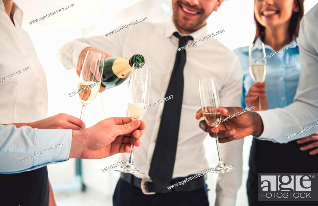 Stock Photo: Cropped image of successful business people drinking champagne, talking and smiling while celebrating in office.
