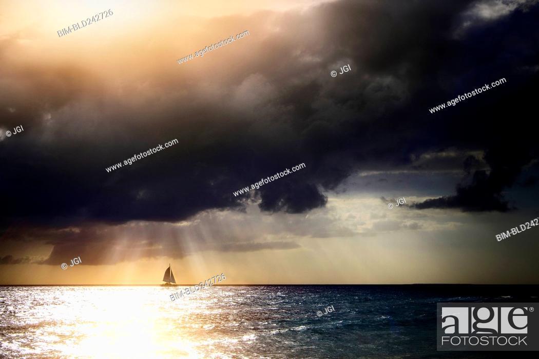 Photo de stock: Sunbeams through storm clouds over sailboat.