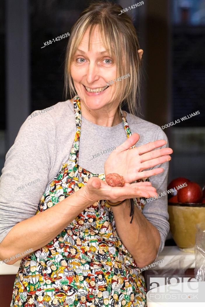 Stock Photo: a woman, 56, prepares meat ball in her kitchen.