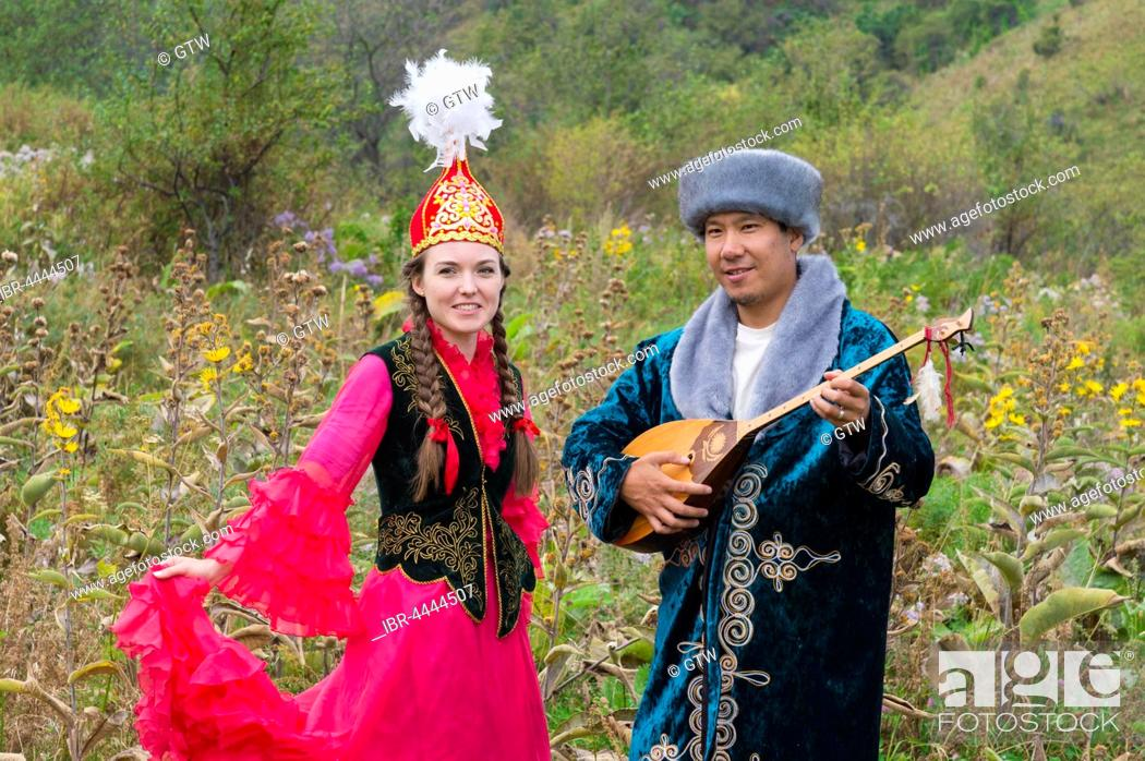 Stock Photo: Kazakh man singing and playing the dombra for a woman, Kazakh ethnographic village aul Gunny, Talgar, Almaty, Kazakhstan.