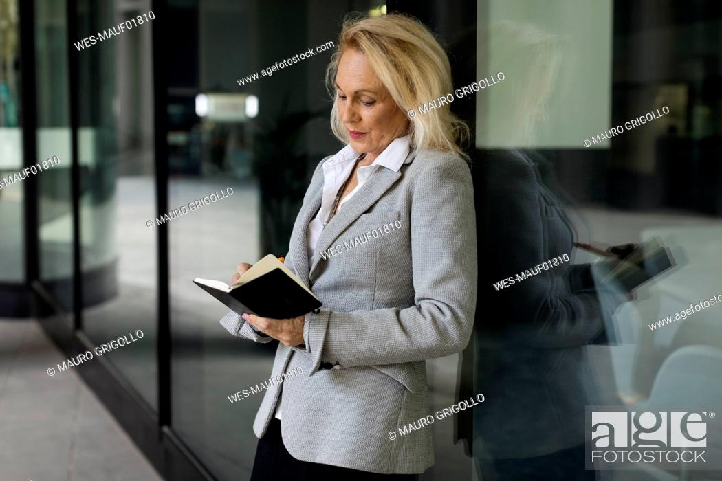 Stock Photo: Senior businesswoman leaning against glass front checking diary.