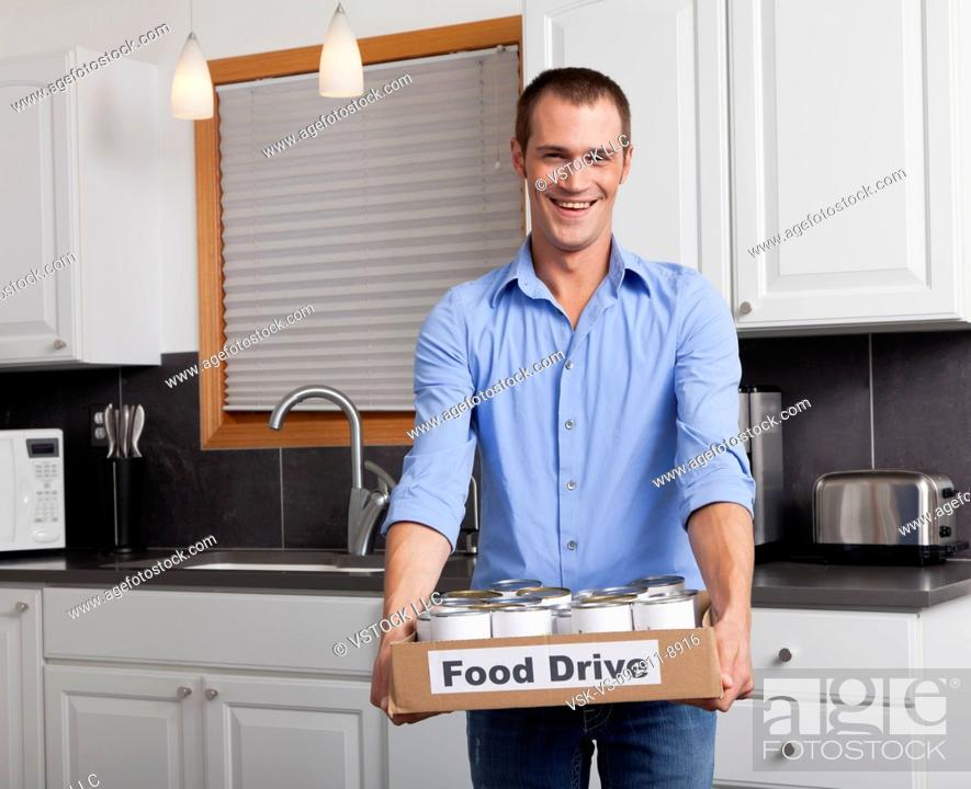 Imagen: USA, Illinois, Metamora, Portrait of smiling man holding cardboard box with canned food in kitchen.