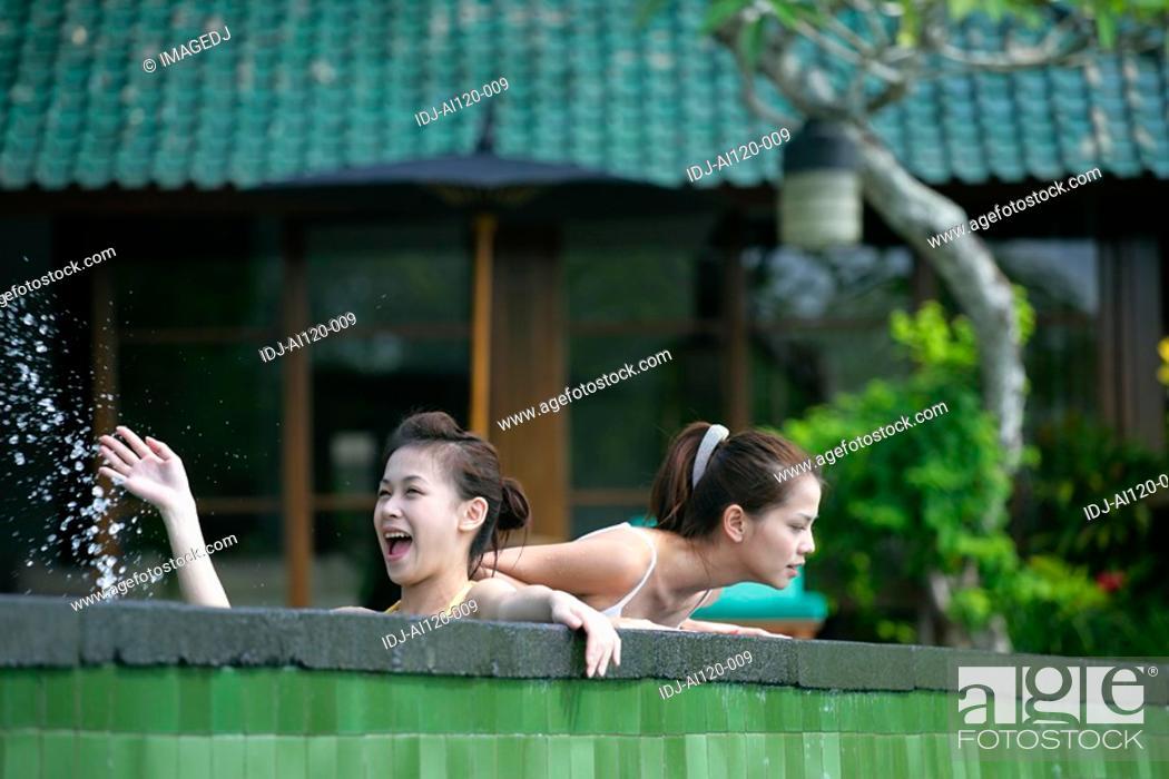 Stock Photo: Two teenage girls near boundary wall.