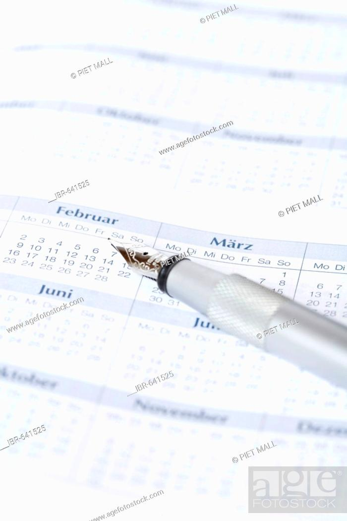 Stock Photo: Pen laying on a calendar.