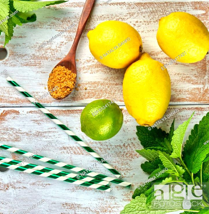 Stock Photo: ripe yellow whole lemons and lime, brown sugar and a bunch of fresh mint on a white wooden board, ingredients for lemonade, copy space.