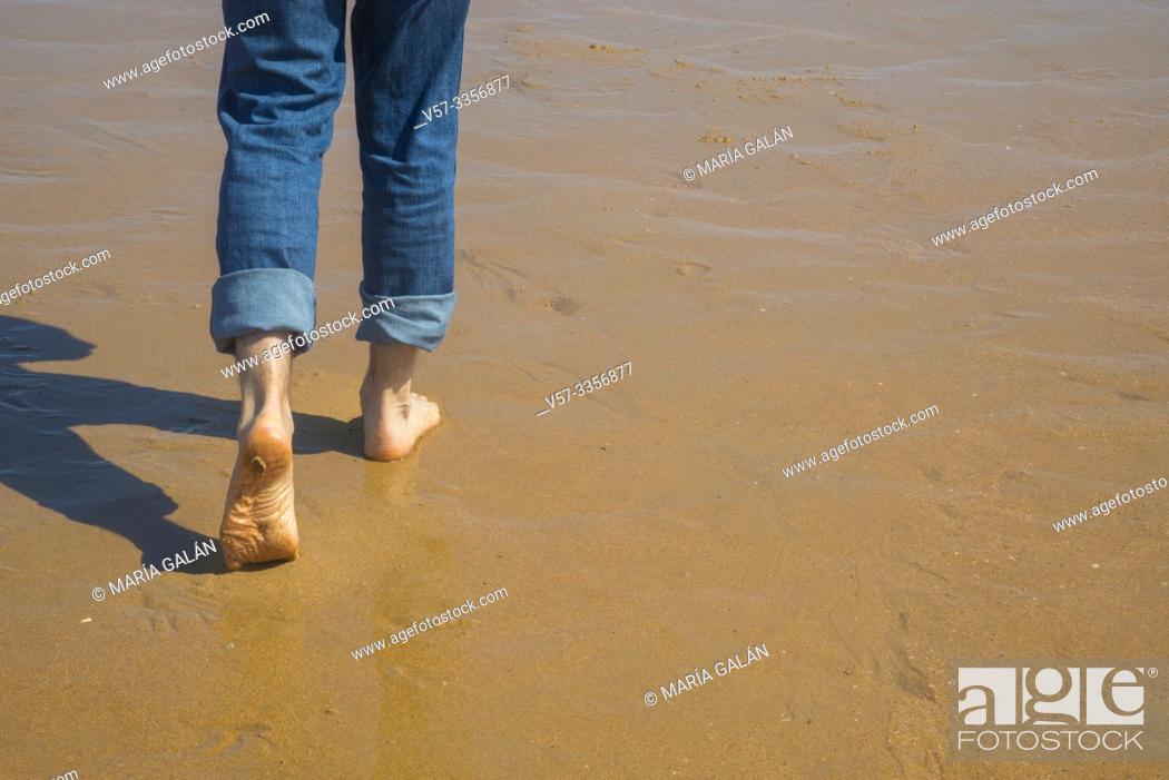Imagen: Man' s legs walking along wet sand.