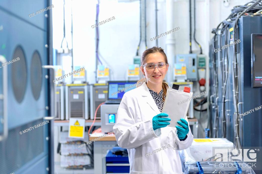 Imagen: Portrait of female scientist holding lithium ion pouch battery in battery research facility.
