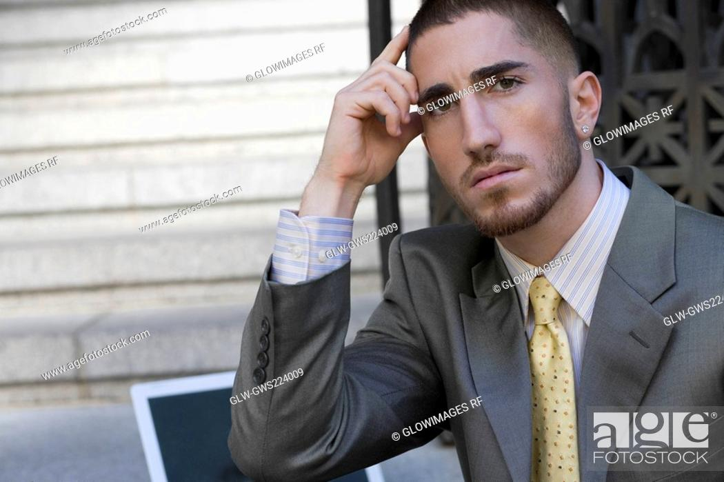 Stock Photo: Portrait of a businessman thinking with his head in his hand.