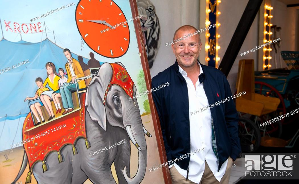Stock Photo: 29 June 2020, Bavaria, Weßling: Heino Ferch, actor, takes part in a press tour at Circus Krone Farm and stands next to an old circus poster.