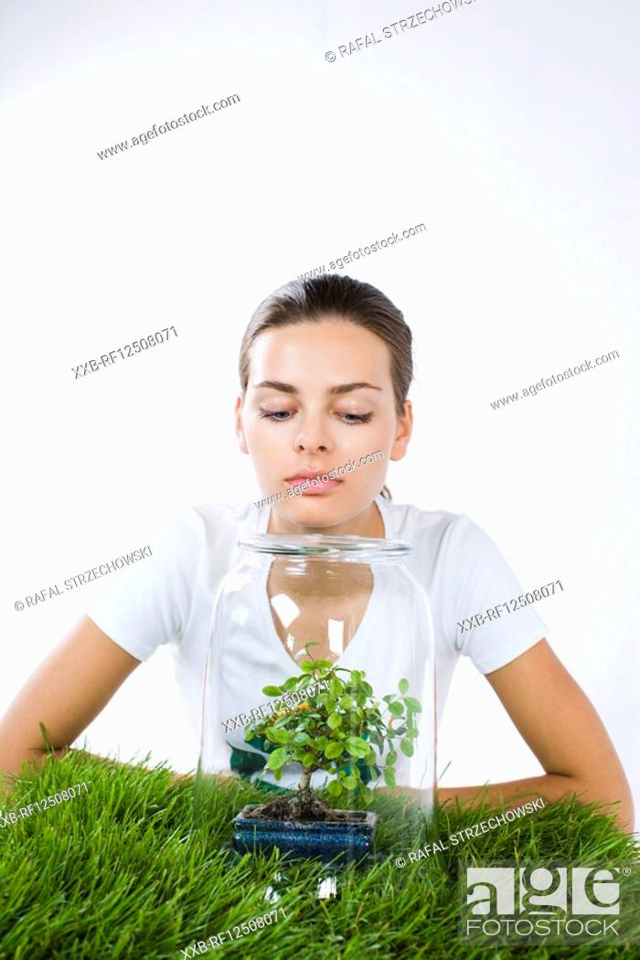 Stock Photo: young woman growing small tree.