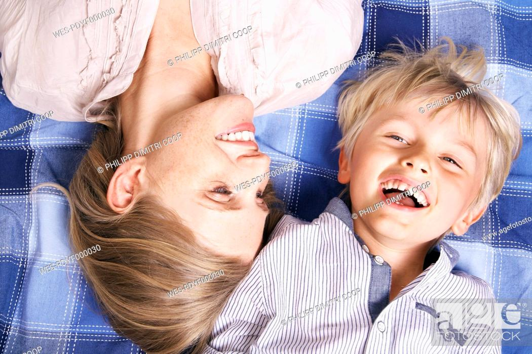 Stock Photo: Germany, Cologne, Mother and son lying on blanket, smiling.