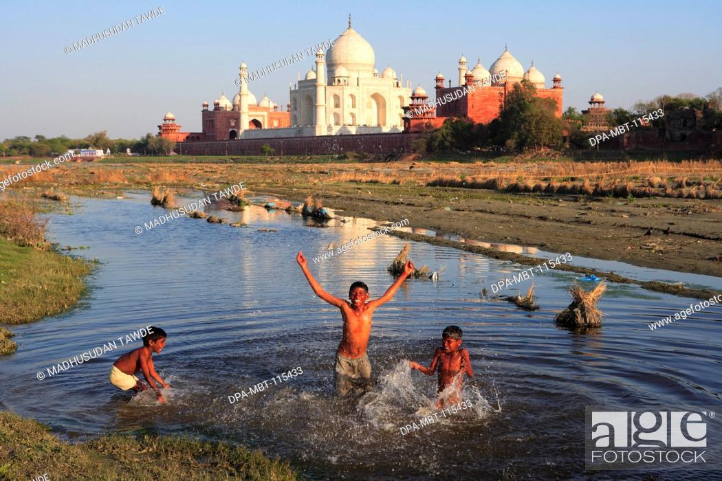 Stock Photo: Children playing in Yamuna river at Taj Mahal Seventh Wonders of World , Agra , Uttar Pradesh , India UNESCO World Heritage Site.