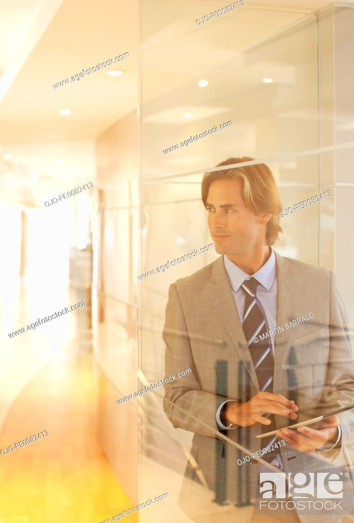 Stock Photo: Businessman with digital tablet in office window.