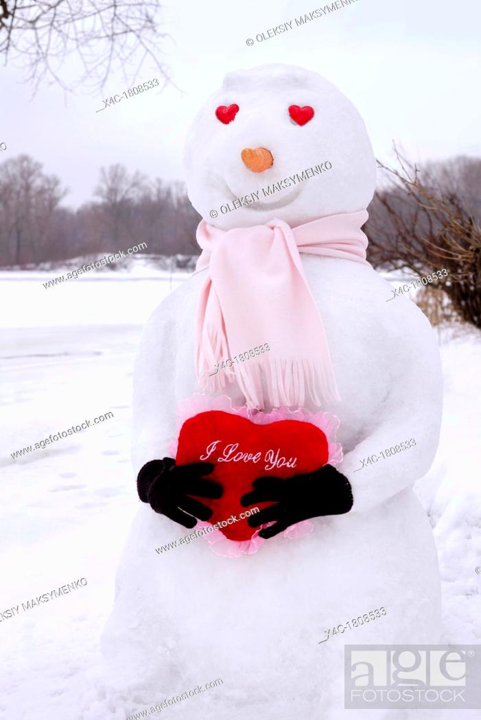 Stock Photo: Smiling snowman with heart-shaped eyes holding a red heart with I Love You written on it in his hands  Winter holidays, Valentine's Day romantic concept.