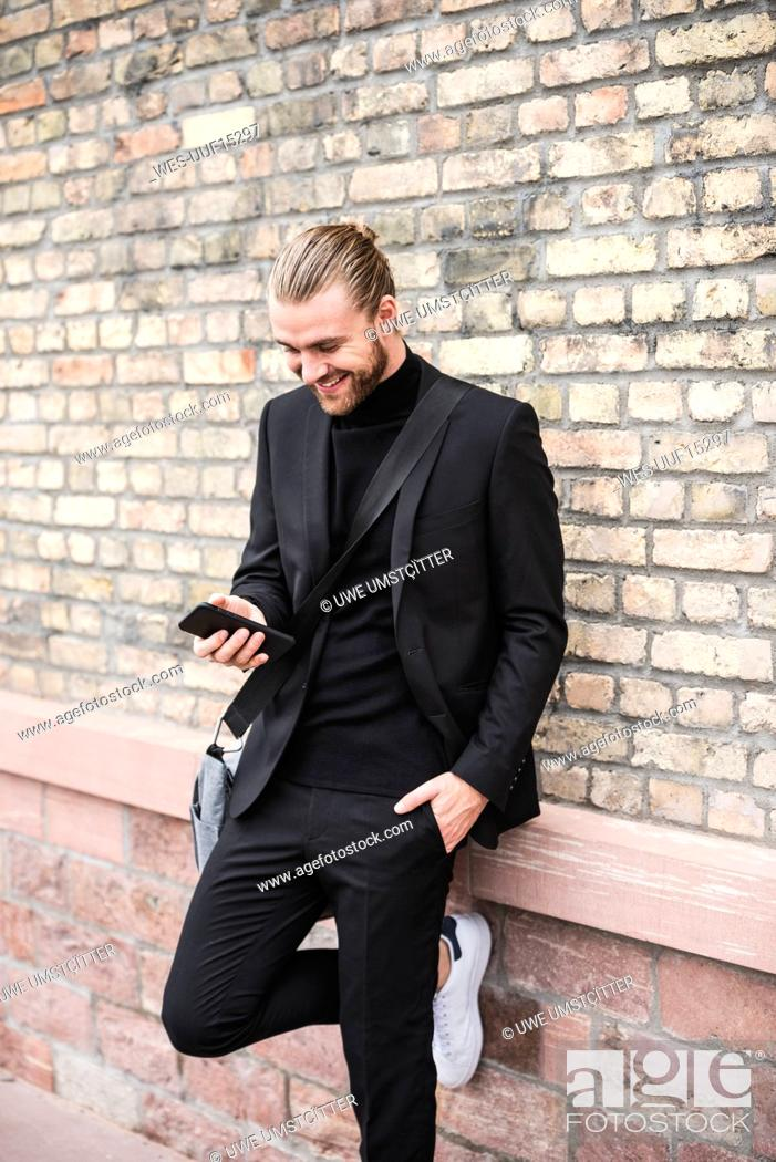 Stock Photo: Smiling fashionable young man leaning against brick wall using cell phone.