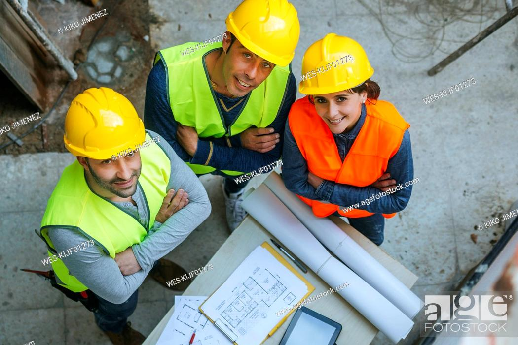 Stock Photo: Portrait of smiling woman and two men in workwear with construction plan.