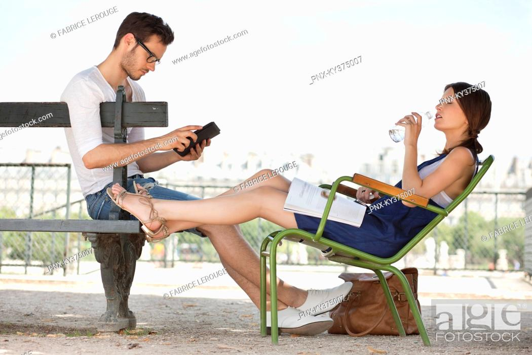 Stock Photo: Woman drinking water and her husband using a digital tablet, Jardin des Tuileries, Paris, Ile-de-France, France.