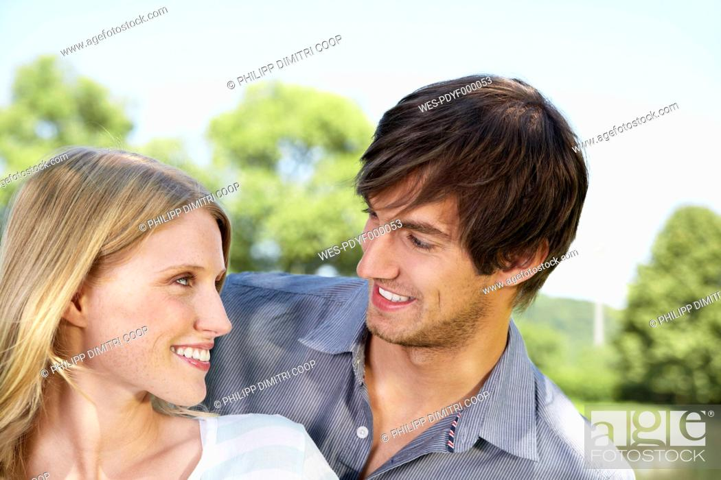 Stock Photo: Germany, Cologne, Young couple looking at each other, smiling.