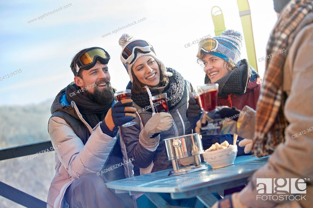 Photo de stock: Skier friends drinking and eating at balcony table apres-ski.