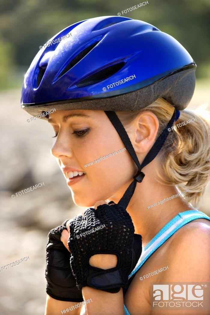 Stock Photo: Caucasian mid-adult woman putting on bicycle helmet.