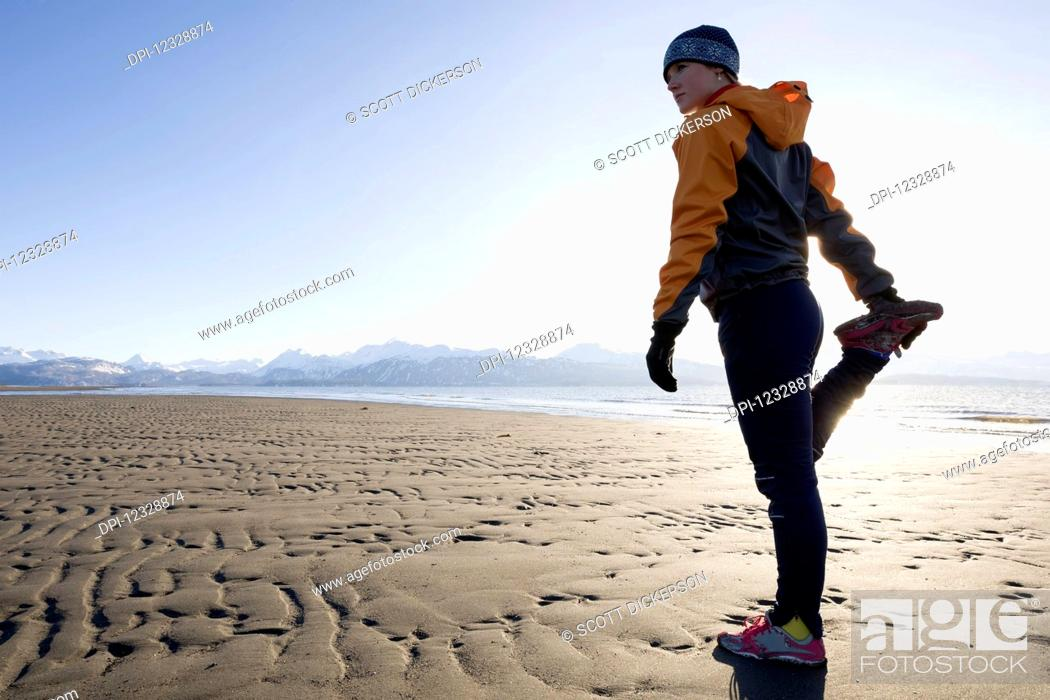 Photo de stock: A Young Woman Stretches On The Wet Beach Before Running; Homer, Alaska, United States Of America.