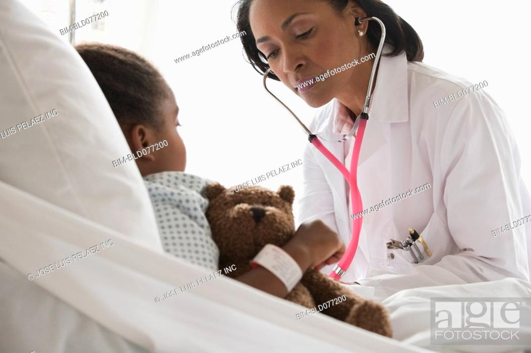 Stock Photo: Doctor examining girl in hospital bed.