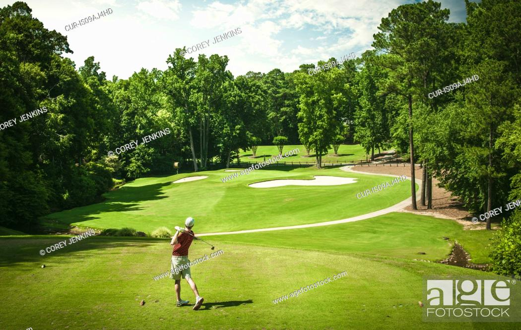 Imagen: Elevated view of young male golfer teeing off on golf course, Apex, North Carolina, USA.