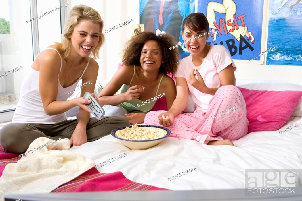 Stock Photo: Three teenage girls 15-17 sitting on bed with popcorn, smiling, portrait.