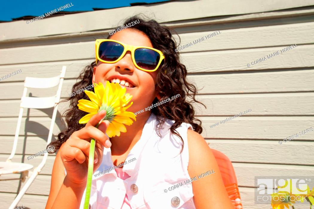 Stock Photo: Portrait of girl wearing yellow sunglasses holding sunflower on patio.