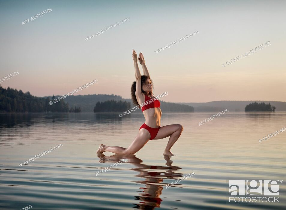 Stock Photo: Young woman practicing Hatha yoga Low Lunge on a floating platform in water on the lake during misty sunrise in the morning. Yoga Anjaneyasana posture.