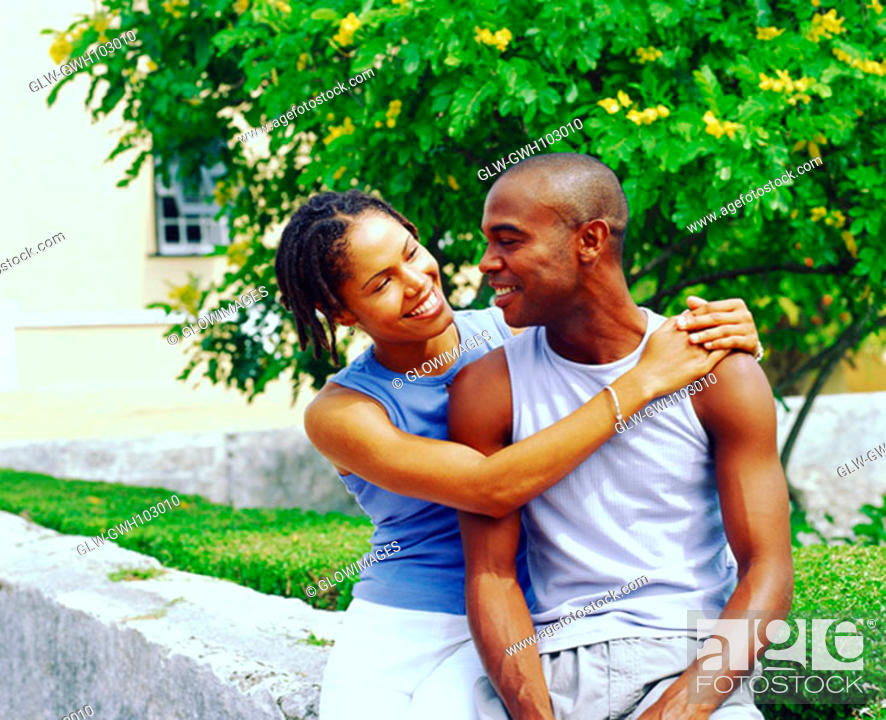 Stock Photo: Close-up of a young woman embracing a young man and smiling, Bermuda.