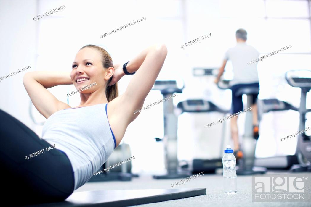 Stock Photo: Smiling woman doing sit-ups in gymnasium.