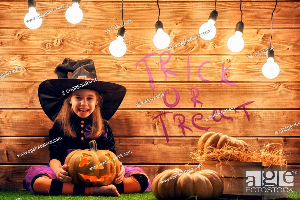 Stock Photo: Happy Halloween! Cute little witch with a pumpkin.