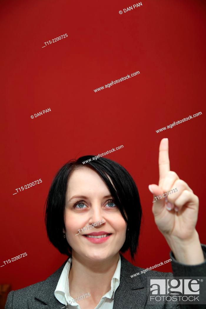 Stock Photo: A black haired young woman pointing her finger up.