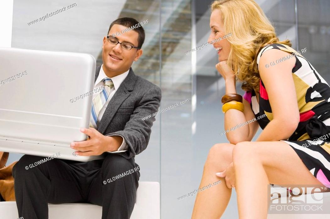 Stock Photo: Businessman holding a briefcase with a mature woman sitting beside him.