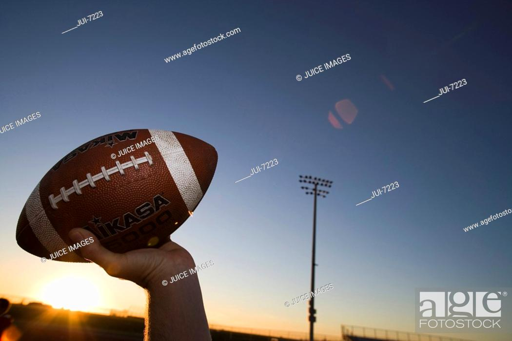 Stock Photo: American football quarterback about to throw ball during competitive game on pitch at sunset, close-up, profile lens flare.